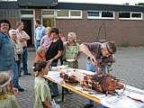 """Indianerhäuptling """"Krummer Hund"""" (Rektor Heinz Müller) beim Zerteilen des Spanferkels"""