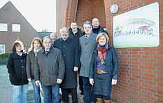 Gemeinsam brachten Vertreter der Lehrer, Eltern, Gemeinden und des Fördervereins das neue Logo am Eingang des Schulgebäudes in Renkenberge an. Foto: Willy Rave/Ems-Zeitung vom 07.12.2010