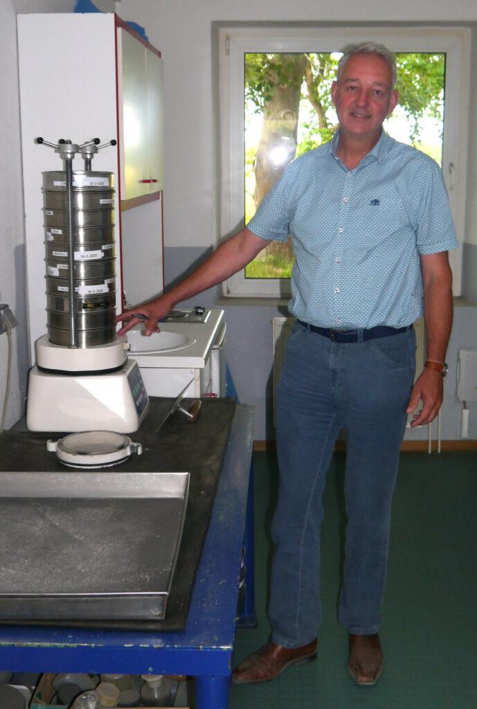 Smals-Projektmanager Paul Hartman im Wippinger Büro neben einem Gerät zur Qualitätskontrolle von Sanden.